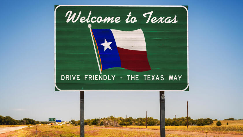 "A photo of a road sign that reads ""Welcome to Texas. Drive Friendly – The Texas Way"""