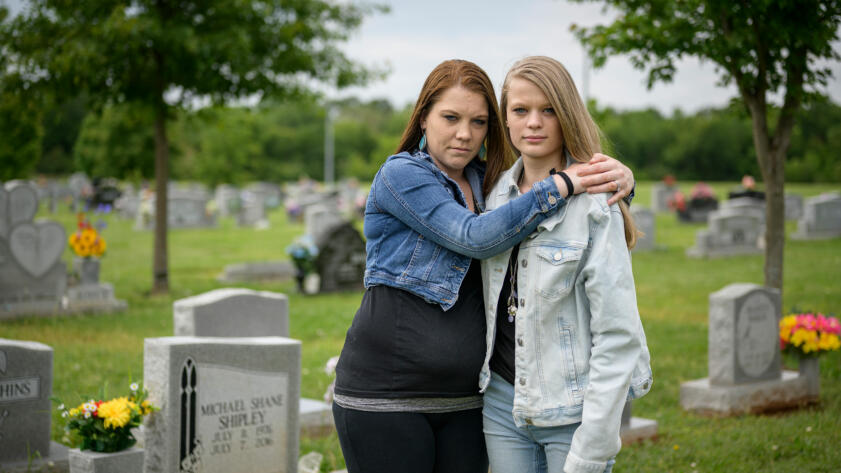 A photo of sisters Brittany Conway and Chelsey Shipley by the grave of their father Michael Shipley who died of a drug overdose