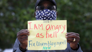 "A Floridan protester holds up a sign that reads ""I am angry as hell. fix unemployment now"""
