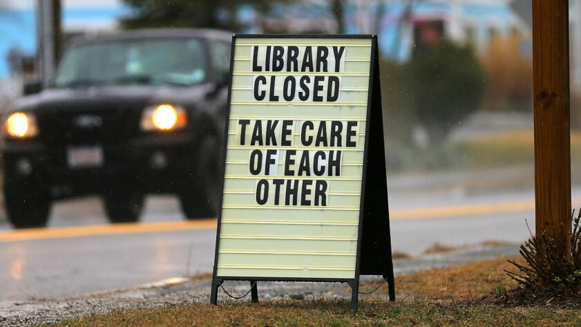 "A sign displayed on the lawn of West Dennis Library, Massachusetts on March 18. The library is still ""closed until further notice"""