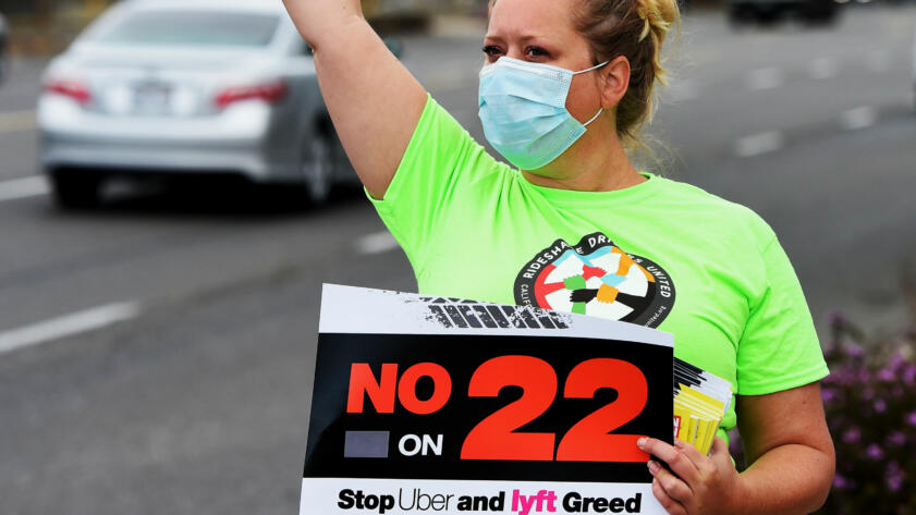 """A Rideshare driver shouts to drivers while holding up a sign that reads """"No on 22"""""""
