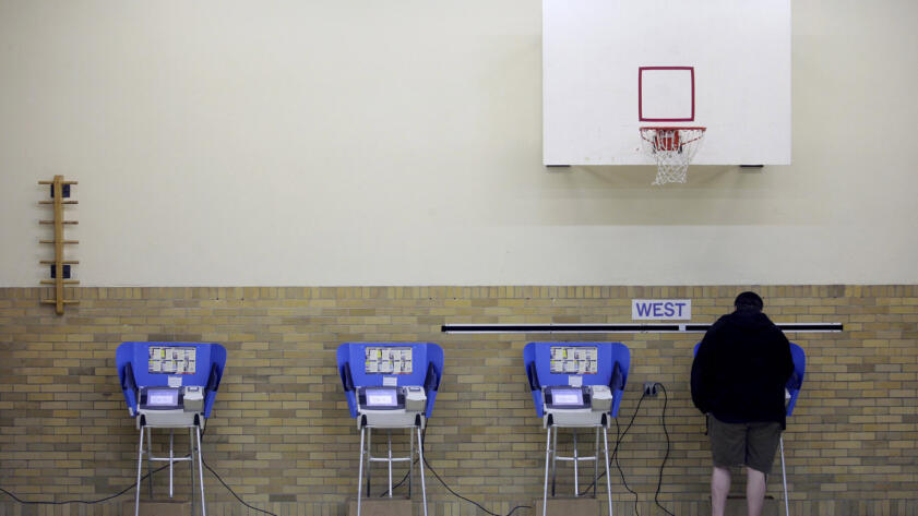 A photo of a man casting his ballot using an electronic voting machine
