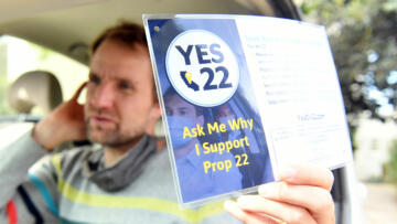 A photo of a rideshare driver holding up a 'Yes on Prop 22' sign