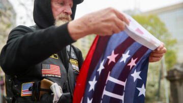 A photo of a man folding a Three Percent flag