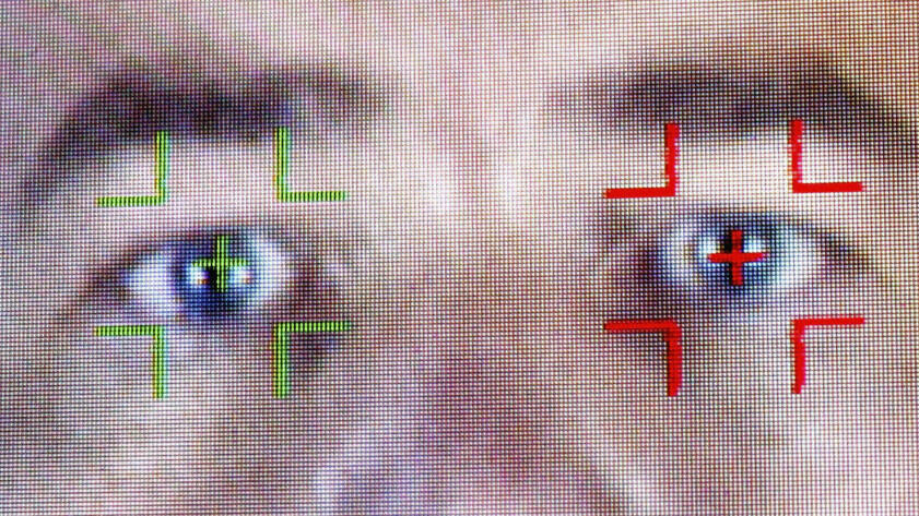 A closeup photo of a pair of eyes being scanned with facial recognition software