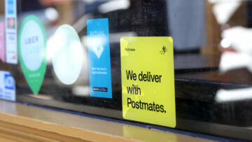 A photo of a 'We deliver with Postmates' sticker in the window of a restaurant in San Francisco