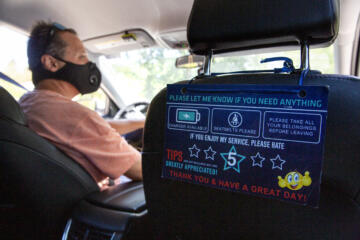 A guest rating placard hangs from the passenger seat of Hector Castellanos' car.