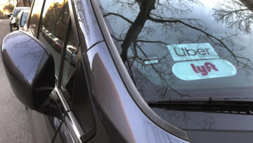 Uber and Lyft sign in windshield of car, Queens, New York.