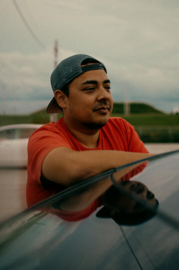 Lenny Sanchez, in a ball cap and orange T-shirt, leans his arm against the back windshield of a car.