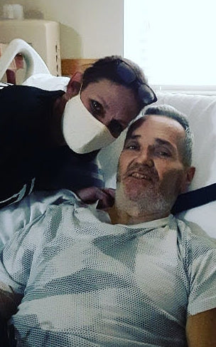 Photo of masked Sheryl Cross leaning over Tommy in hospital bed