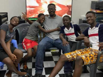 Photo of Elijah Newman on a couch surrounded by four of his children in Ghana