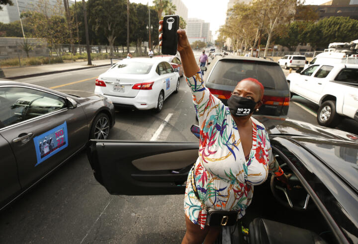 A masked woman, surrounded by parked cars in a demonstration, holds up a cell phone.