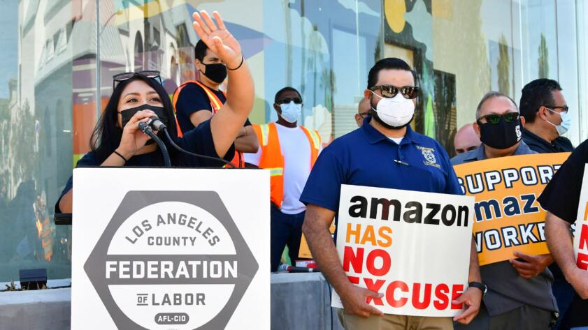 A masked woman stands behind a podium with her hand raised. People next to her are holding signs criticizing Amazon.