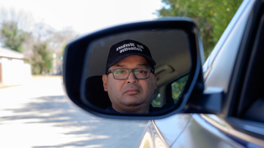 """Photograph of a man's reflection in a car's side view mirror. He is wearing a hat that says """"Gig Workers Collective"""""""