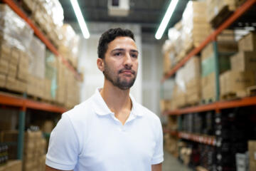 Photograph of a man in a white polo shirt standing in a warehouse.