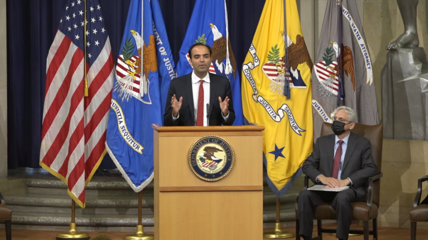 Rohit Chopra stands at a podium in the Department of Justice auditorium.